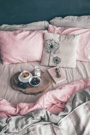 Black loft bedroom and pastel bedding set. Unmade bed with breakfast and reading on tray. Interior decor over blackboard wall. Cozy modern living space. Stok Fotoğraf - 81879741