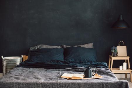 Dormitorio loft estilo negro. Cama sin desayunar con desayuno y lectura en la bandeja. Decoración de la lámpara y del interior sobre la pared en blanco de la pizarra con el copyspace. Acogedor espacio de vida moderna.