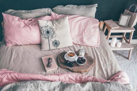 Black loft bedroom and pastel bedding set. Unmade bed with breakfast and reading on tray. Interior decor over blackboard wall. Cozy modern living space. Stockfoto