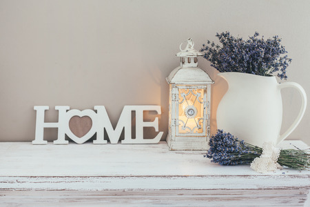 Shabby chic interior decor for farmhouse. Lavender in pitcher, lantern and wooden letters on a vintage shelf over pastel wall. Provence home decoration.