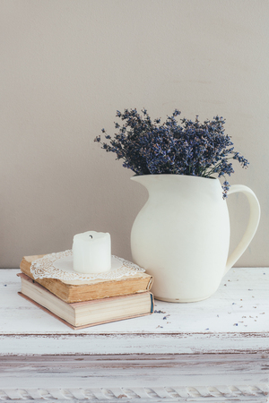 Shabby chic interior decor for farmhouse. Lavender in pitcher, books and candle on a vintage shelf over pastel wall. Provence home decoration.