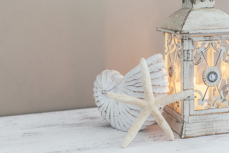 Beach wedding interior decor. Natural seashell and lantern on vintage shelf over pastel wall. Stock Photo