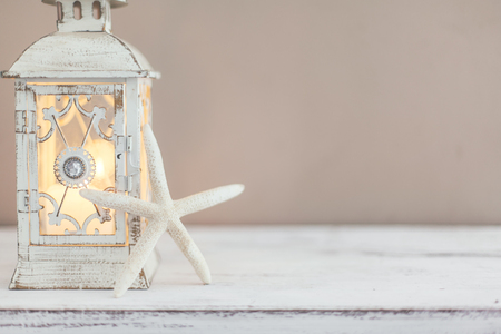 Beach wedding interior decor. Natural seashell and lantern on vintage shelf over pastel wall. 版權商用圖片