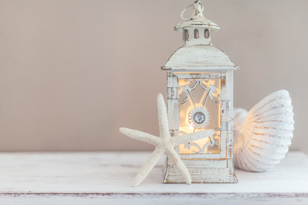 Beach wedding interior decor. Natural seashell and lantern on vintage shelf over pastel wall. Imagens