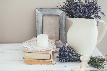Shabby chic interior decor for farmhouse. Lavender in pitcher, books and blank photo frame on a vintage shelf over pastel wall. Provence home decoration.