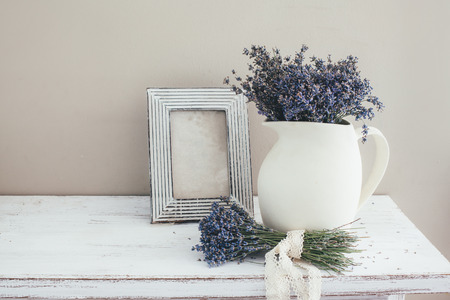 Shabby chic interior decor for farmhouse. Lavender in pitcher and blank photo frame on a vintage shelf over pastel wall. Provence home decoration.