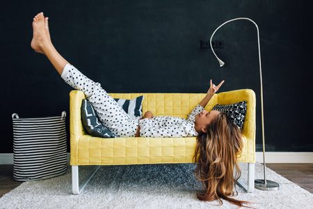 Home portrait of pre teen child girl wearing pajama relaxing and chilling on the yellow couch against black wall in modern living room interior