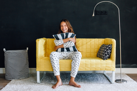 Home portrait of pre teen child girl wearing pajama resting and chilling on the yellow couch against black wall in modern living room interior