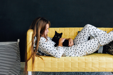 Home portrait of pre teen child girl wearing pajama hugging her cat on the yellow couch against black wall in modern living room interior photo
