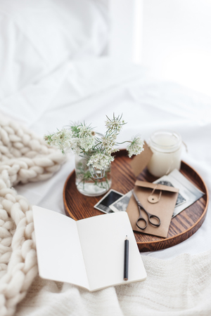 Wooden tray with paper notebook, old photos, candle and spring flowers on white bedding. Relaxing, or working, or writing diary or blog in bed at home. Archivio Fotografico
