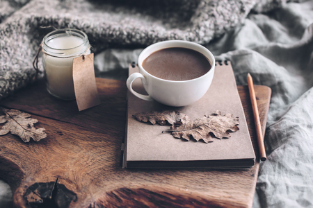 Cup of coffee and candle on rustic wooden serving tray with blanket. Spending autumn weekend in the cozy bed. Stock Photo