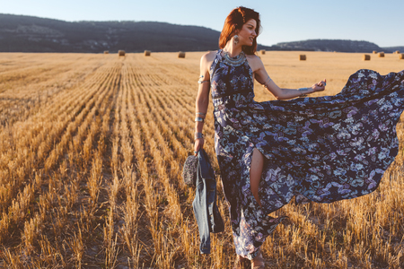 Beautiful model wearing summer cotton maxi dress and jewelery posing in autumn field with hay stack. Boho style clothing and jewelry. Stock Photo
