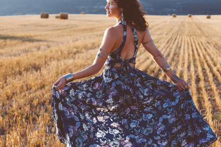 Beautiful model wearing summer cotton maxi dress and bracelets posing in autumn field with hay stack. Boho style clothing and jewelry. Stock Photo