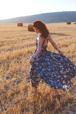 Beautiful model wearing summer cotton maxi dress posing in autumn field with hay stack. Boho style clothing and jewelry. Stock Photo
