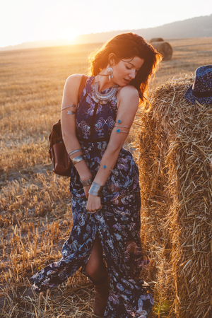 Beautiful model wearing summer cotton maxi dress posing in autumn field with hay stack. Boho style clothing and jewelry. photo