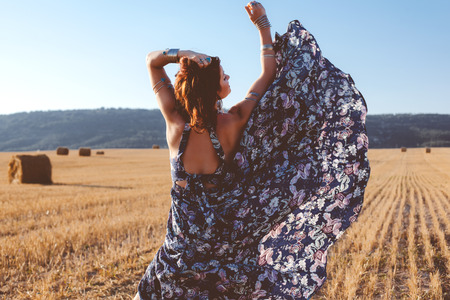 Beautiful model wearing summer cotton maxi dress and bracelets posing in autumn field with hay stack. Boho style clothing and jewelry. photo