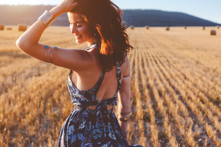 Beautiful model wearing summer cotton maxi dress and bracelets posing in autumn field with hay stack. Boho style clothing and jewelry. Standard-Bild