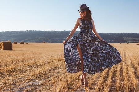 아름 다운 모델 입고 여름 목화 맥시 드레스 건초 스택과 함께을 필드에 포즈. Boho 스타일의 의류 및 보석.
