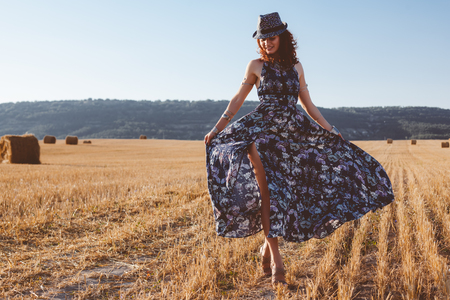 Beautiful model wearing summer cotton maxi dress posing in autumn field with hay stack. Boho style clothing and jewelry. Standard-Bild