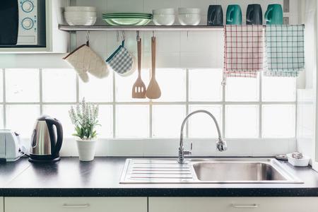家庭の台所のインテリア。手すりシステムとウィンドウ上の皿が付いている棚の調理器具。