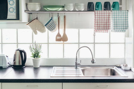 Home kitchen interior. Cooking utensils on a railing system and shelf with dishes above a window. Reklamní fotografie - 84141634