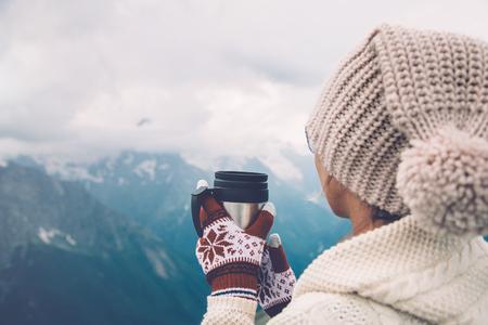 Closeup Foto von thermischen Becher mit Tee in Reisenden Hände über Berge Blick mit Schnee, Tourizm in kalten Jahreszeit photo
