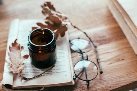 Warme en gezellige scène met oud boek en kaars op een tafel. Herfstweekend, herfstlevensstijl. Stockfoto
