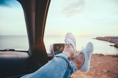 Fall car trip in sunset. Freedom travel concept. Spending weekend in roadtrip. Woman feet on car window, wathing the sea.