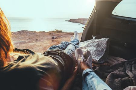 Man en vrouw ontspannen binnen kofferbak en kijken naar de zee. Vallen autotocht in zonsondergang. Freedom travel concept. Herfstweekend. Stockfoto