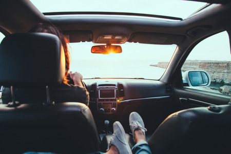 Fall car trip in sunset. Freedom travel concept. Spending weekend in roadtrip. Woman feet on car dashboard.