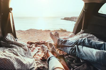 男と女のトランクの中リラックスして海を見てします。日没で秋の車旅。自由旅行の概念。秋の週末。