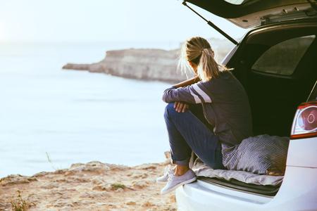 Mujer que relaja dentro del tronco del coche y que mira en el mar. Viaje de otoño al atardecer. Concepto de viaje de la libertad. Fin de semana de otoño. Foto de archivo