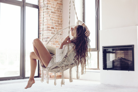 Young woman chilling at home in comfortable hanging chair in front of big window. Girl relaxing in swing in loft living room with brick walls.