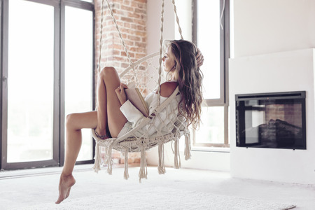 Young woman chilling at home in comfortable hanging chair near fireplace. Girl relaxing and reading book in swing in loft living room with brick walls. Standard-Bild