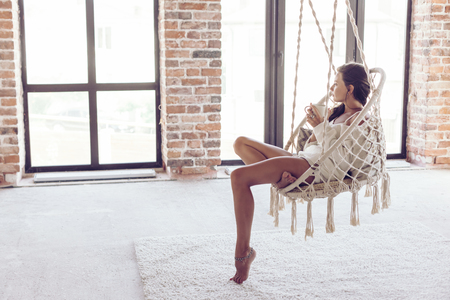 Young woman chilling at home in comfortable hanging chair in front of big window. Girl relaxing in swing in loft living room with brick walls. Beautiful legs barefoot on white carpet.