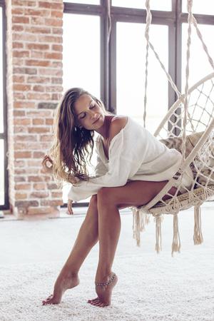 Jonge vrouw chillen thuis in comfortabele hangende stoel voor het grote raam. Meisje ontspannen in swing in loft woonkamer met bakstenen muren. Mooie benen blote voeten op wit tapijt.