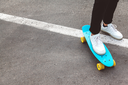 Girl wearing fashion sportswear rollerskating on skateboard in the city street, urban hipster style, feet in shoes closeup