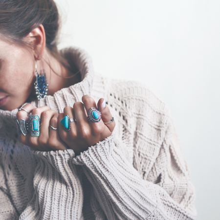 Boho jewelry on model: ethnic stone rings and earrings. Beautiful woman wearing warm woolen sweater and fashion jewellery. Minimal style and pastel tone. Stock Photo - 84633552