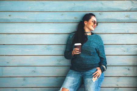 La mujer hermosa que lleva el suéter de la caída, los pantalones vaqueros rasgados y los vidrios que beben se llevan el café que se opone a la pared del café en la calle de la ciudad. Moda casual, elegante aspecto cotidiano. Modelo de talla grande