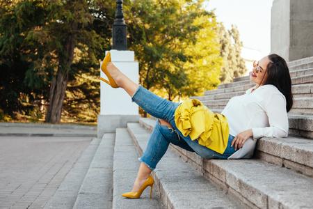 美しい若い女性身に着けている明るいカラフルなジャケット、ジーンズと都市通りを歩いてかかと靴をリッピングします。カジュアルなファッショ