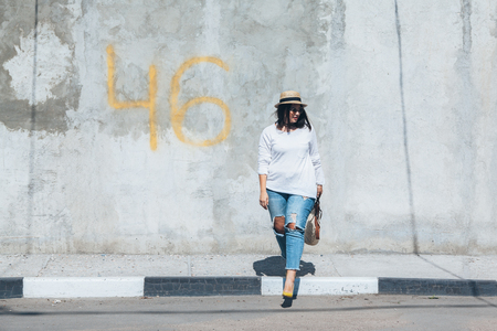Young fashion woman wearing ripped jeans, colorful heels and straw accessories posing over gray concrete city wall. Plus size model. 免版税图像