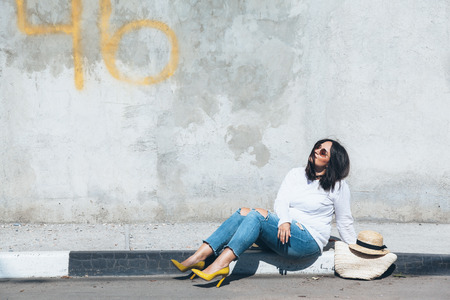 Young fashion woman wearing ripped jeans, colorful heel shoes and straw accessories posing over gray concrete city wall. Plus size model. Imagens