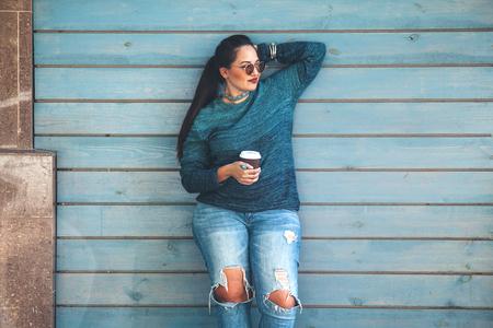 Mooie vrouw draagt vallen trui, gescheurde spijkerbroek en glazen drinken wegnemen koffie staande tegen cafe muur op stadsstraat. Casual mode, elegante alledaagse look. Plus maat model. Stockfoto