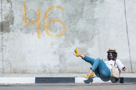Young fashion woman wearing ripped jeans, colorful heel shoes and straw accessories posing over gray concrete city wall. Plus size model. Stockfoto
