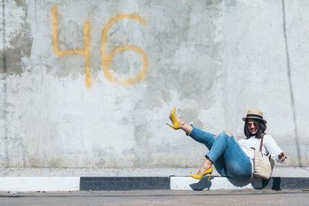 Jonge mode vrouw met gescheurde spijkerbroek, kleurrijke hakskoenen en stro-accessoires die over grijze betonnen stadsmuur staan. Plus maat model. Stockfoto - 87129360