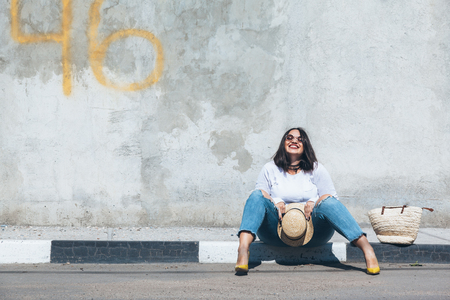 Young fashion woman wearing ripped jeans, colorful heels and straw accessories posing over gray concrete city wall. Plus size model. Stockfoto