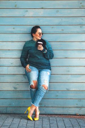 Mooie vrouw draagt vallen trui, gescheurde spijkerbroek en kleurrijke schoenen drinken wegnemen koffie staande tegen cafe muur op stadsstraat. Casual mode, elegante alledaagse look. Plus maat model.