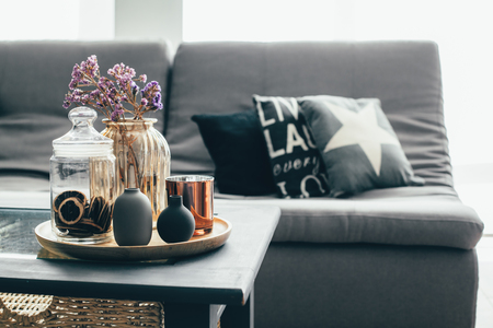 Home interior decor in gray and brown colors: glass jar with dried flowers, vase and candle on the wooden tray on the coffee table over sofa with cushions. Living room decoration. Foto de archivo