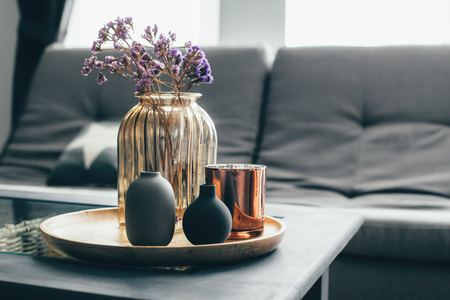 Home interior decor in gray and brown colors: glass jar with dried flowers, vase and candle on the wooden tray on the coffee table over sofa. Living room decoration.