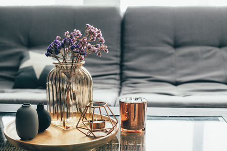 Home interior decor in gray and brown colors: glass jar with dried flowers, vase and candle on the wooden tray on the coffee table over sofa with cushions. Living room decoration. Standard-Bild